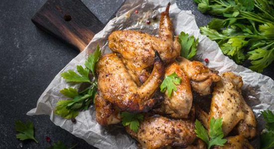 Baked chicken wings. Wings of barbecue on dark stone table.