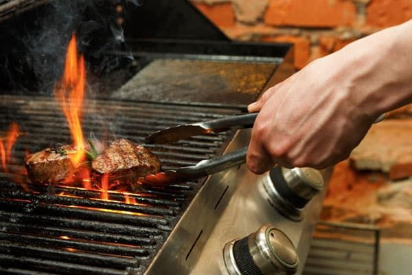 Man cooking bbq meat steaks on professional grill outdoors. Male hand with tongs flipping beefsteaks on open fire