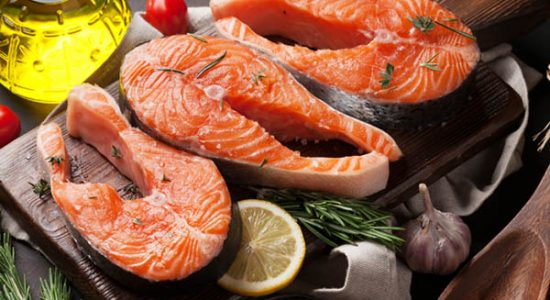 Raw salmon fish fillet with spices cooking on cutting board